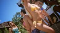 SLO MO kaukasischen Mann und Frau zusammen tanzen in ihren Badeanzügen in einem Pool-party mit ihren Freunden an einem heißen Sommertag