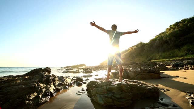 Caucasian man arms outstretched on the beach at sunrise