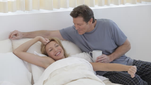 Caucasian man bringing coffee to wife in bed