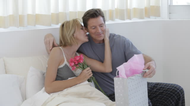 Caucasian man bringing roses to wife in bed