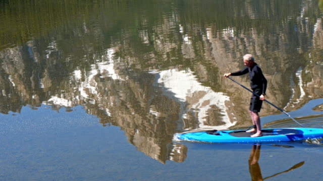 Caucasian man paddleboarding on Stanley Lake, Stanley, Idaho, United States