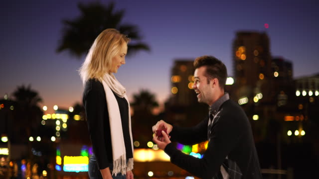 Caucasian man proposes to his girlfriend at night outdoors