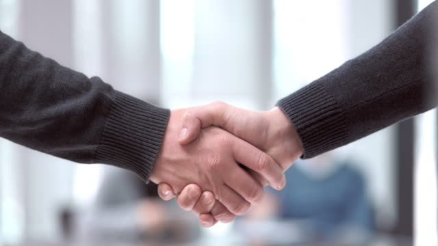 SLO MO PAN Caucasian men handshake in meeting room