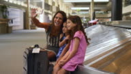 Caucasian mother and daughters posing for cell phone selfie at airport