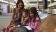 Caucasian mother and daughters waiting at airport watching cell phone
