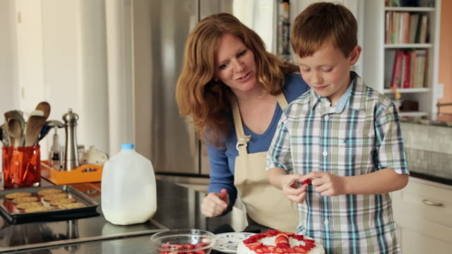 Caucasian mother and son decorating cake