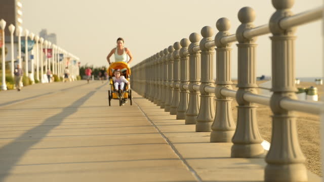 Caucasian mother jogging on boardwalk with baby stroller