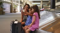 Caucasian mother showing daughter how to use cell phone at airport
