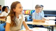 Caucasian private school student enjoys listening to her teacher during class