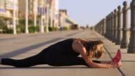 Caucasian teenage girl doing splits on boardwalk