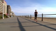 Caucasian teenage girl running on boardwalk