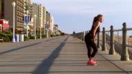 Caucasian teenage girl stretching legs on boardwalk