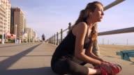 Caucasian teenage girl wearing earbuds stretching legs on boardwalk