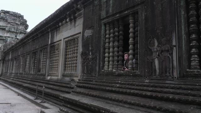 Caucasian Tourist Peering through Columns in Angkor Wat Temple