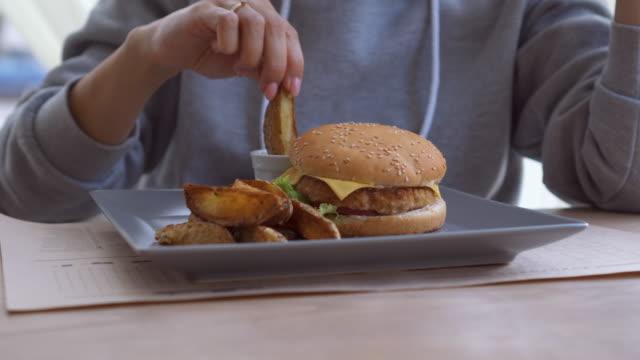 Kaukasische Frau Hamburger und Kartoffeln zu Hause essen