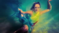 Caucasian woman in dress swimming under water