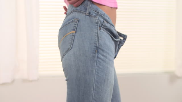 Caucasian woman putting on pants