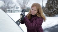 Caucasian woman scraping ice from car