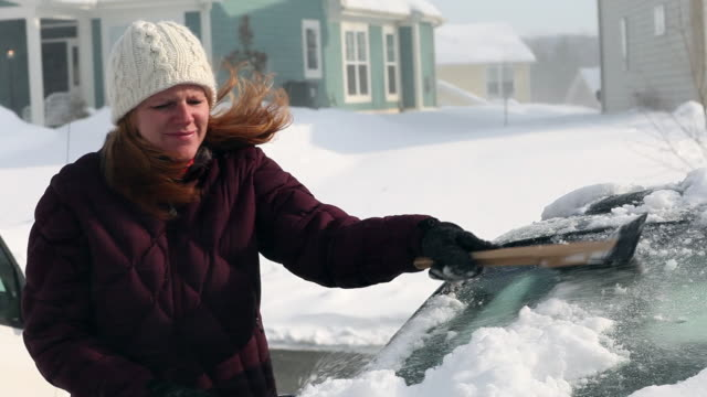 Caucasian woman scraping snow from car