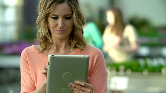 Caucasian woman shops for flowers at greenhouse using tablet