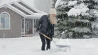 Caucasian woman shoveling snow in front yard