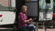 Caucasian woman using digital tablet at trailer