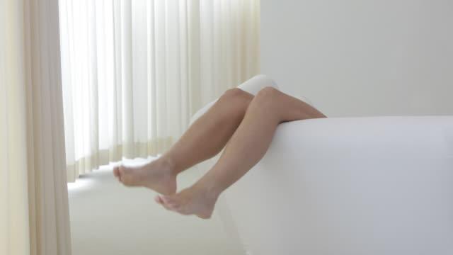 Caucasian woman's legs on sofa