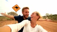 Caucasian young couple take selfie portrait with kangaroo crossing sign