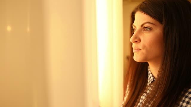 Caucasian young woman looking out the window.