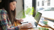 Caucasian young woman working at her laptop in coffee shop.