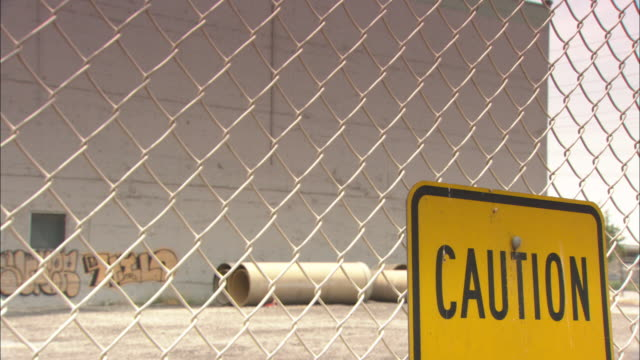 A caution sign hangs on a chain-link fence.