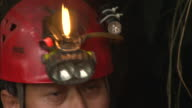 A caver lights the lamp on his helmet before abseiling into a cave. Available in HD.