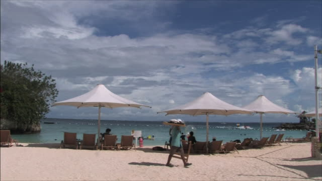 Cebu Sea Beach People resting in deckchairs under the parasol From behind Long Shot
