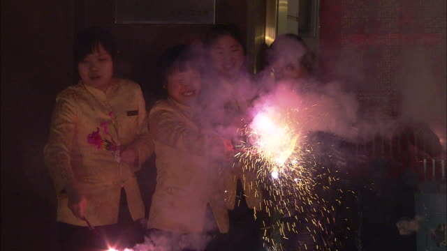 Celebrants wave lighted fireworks and sparklers on the street for Chinese New Year.