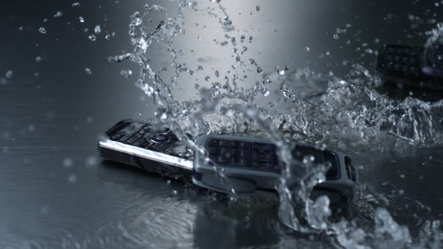 Cell phone crashing in puddle, slow motion-close up