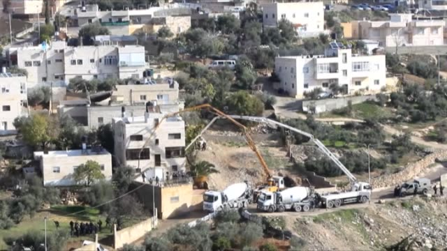 Cement mixers belonging to the Israeli authorities pump concrete into the house of Palestinian Alaa Abu Jamal who allegedly carried out an attack in...