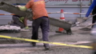 Cement pours out of truck along city sidewalk while construction workers smooth it out as cars pass through the frame.