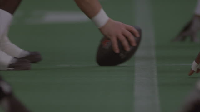 A center prepares to snap the ball during a football game.