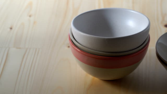PAN/Ceramic bowls stacked on wooden floor.