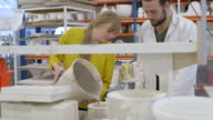 Ceramic designer pouring clay into mold in workshop