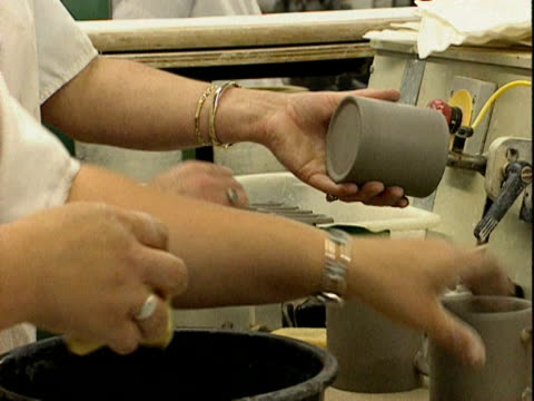 Ceramic mugs have handles added prior to firing and glazing in a pottery factory England 1999