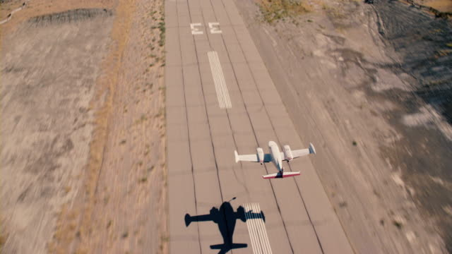 A Cessna airplane launches into flight and soars above mountains and desert terrain.