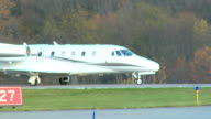 Cessna Citation Excel private jet plane taxiing across frame on runway at airport