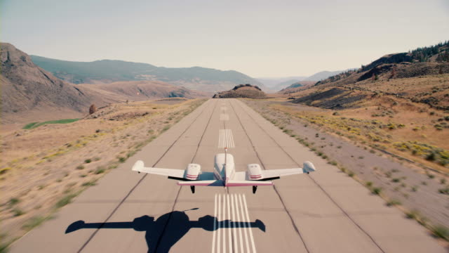 A Cessna commuter airplane picks up speed down a desert runway before it takes off and flies over mountains and desert terrain.