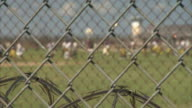 Chain link fence w/ razor wire BG SOFT BG Male inmates prisoners walking across prison yard Prison fencing security incarceration not jail...