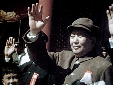 Chairman Mao waves at marching students carrying flowers / students release balloons / drummers march in formation with red sashes /