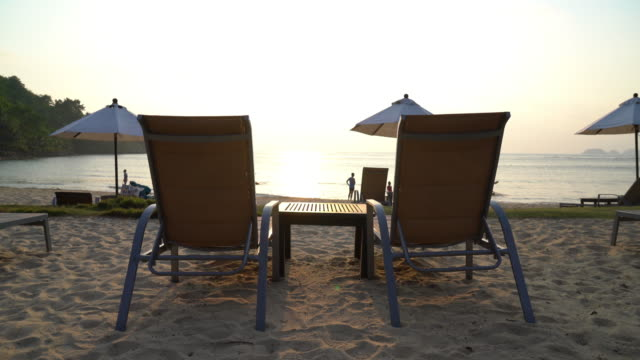 Chairs and umbrella on tropical beach at sunset