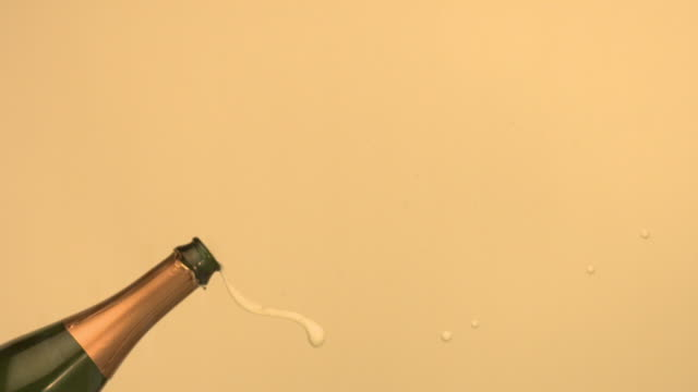 Champagne cork popping out of bottle (slow motion)