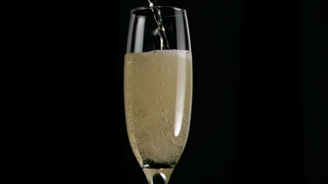 Champagne flowing in super slow motion in a flute