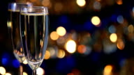 Champagne glasses with Christmas lights in the background